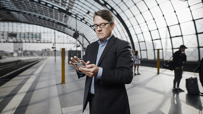 Mann steht mit Handy auf Bahnsteig