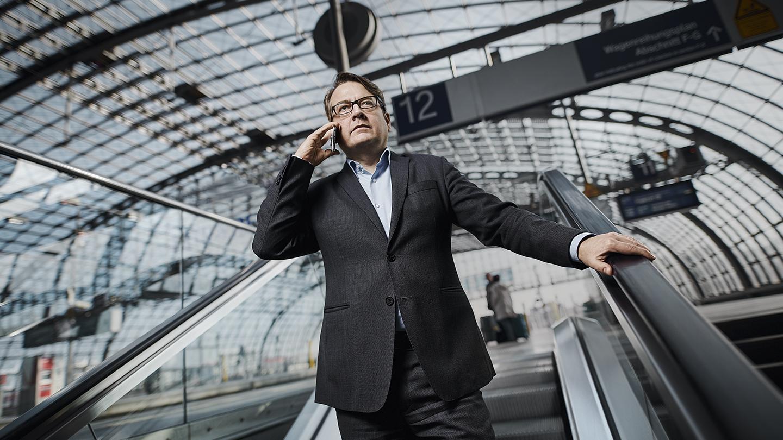 Mann telefoniert auf der Rolltreppe im Bahnhof