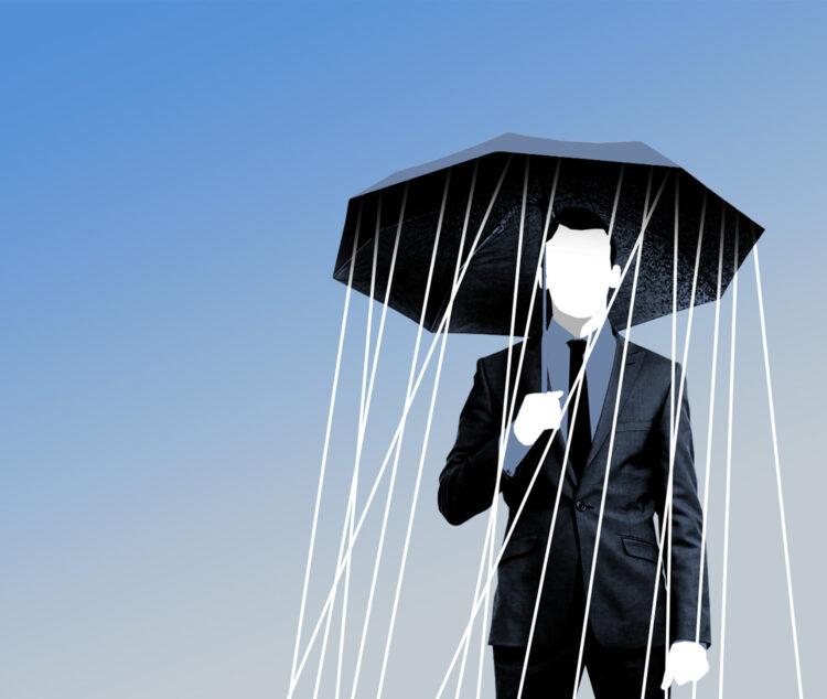 Mann in Anzug steht mit Schirm unter dem es regnet